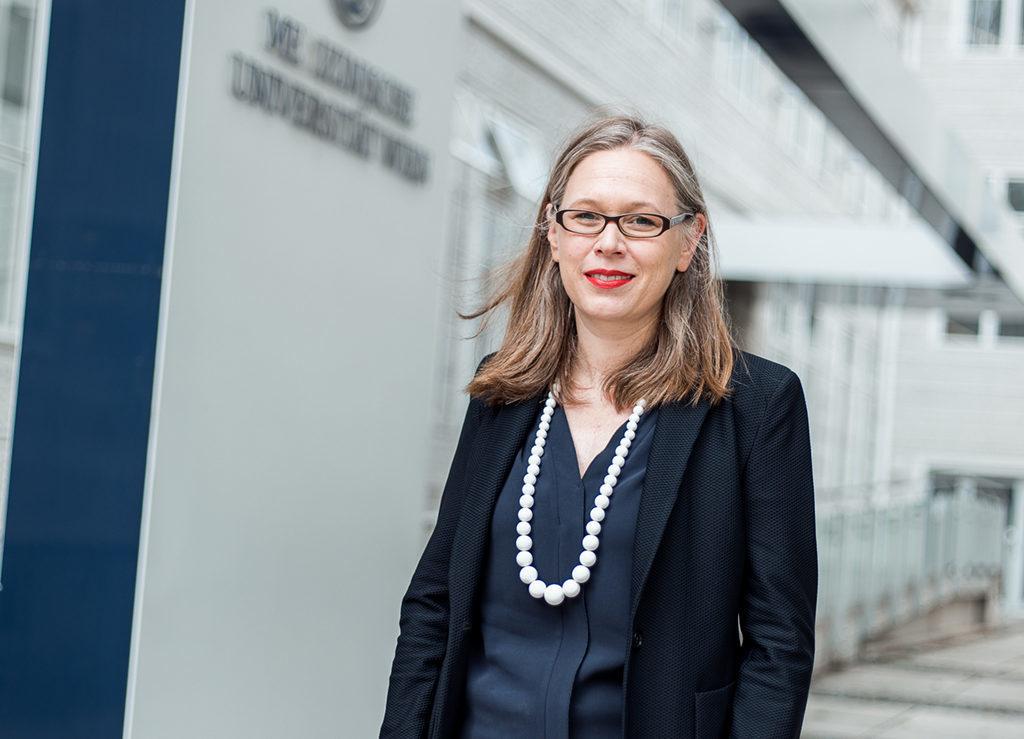 Michaela Fritz steht leicht lächelnd vor einem Gebäude der Medizinischen Universität Wien. Der Wind bläst durch ihre offene Haare, sie trägt eine Brille, roten Lippenstift und eine große weiße Perlenkette um den Hals.